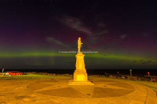 Captain Cook Looks Over Whitby With A Stunning Aurora Borealis In The Night Time Sky