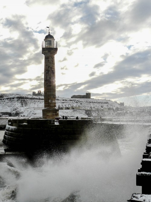 Whitby West Pier LightHouse With A Snowy Whitby In The Backdrop. Heavy snows had fallen over night and the whole of Whitby had a good covering. What made things even more special that morning was the huge waves rollin g in from The South East. This swell direction usually means they roll up the inside of The West Pier and then crash into the wall at the bull noses.