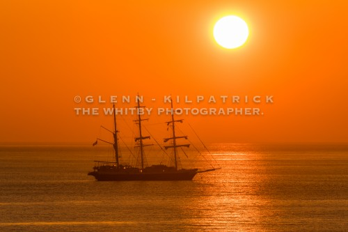 Taken from Sandsend cliffs on Sunday, 9 April 2017, The Lord Nelson, a frequent visitor to The Yorkshire Coast is seen at anchor with a giant orange sun rising from the sea.