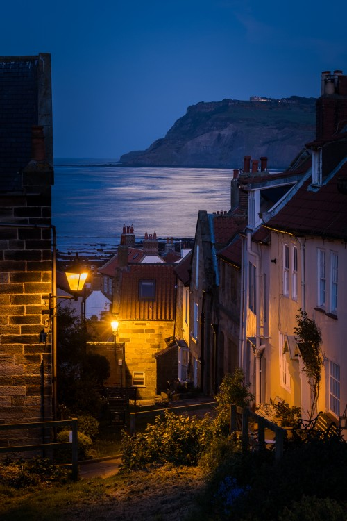 Fisherhead At Robin Hoods Bay With Moonlight On The Water And Ravenscar Cliffs Behind