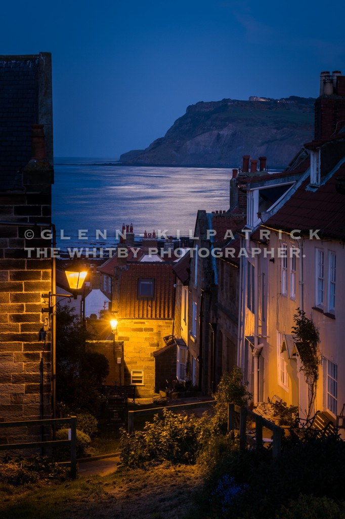 Robin Hoods Bay with a moonlit path across the water to Ravenscar.